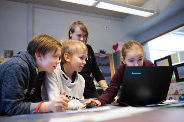 Oppilaat opettajan kanssa tietokoneen ääressä