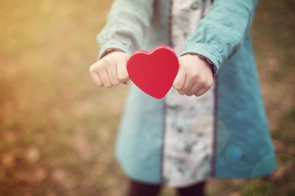 Tyttö pitelee käsissään punaista sydäntä