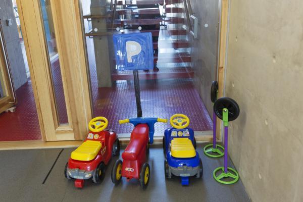 Barns sparkbilar på daghemmets parkeringsplats.