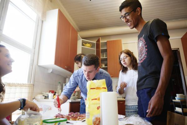 Kuvituskuvassa nuoret aikuiset valmistavat ruokaa kodinomaisessa ympäristössä