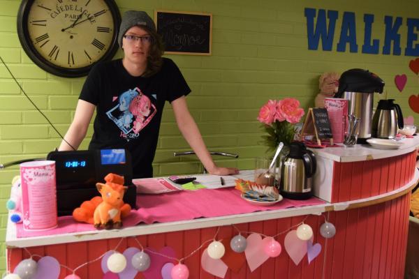 Ystävänpäiväkahvilan tiski, jonka takana seisoo asiakaspalvelija.