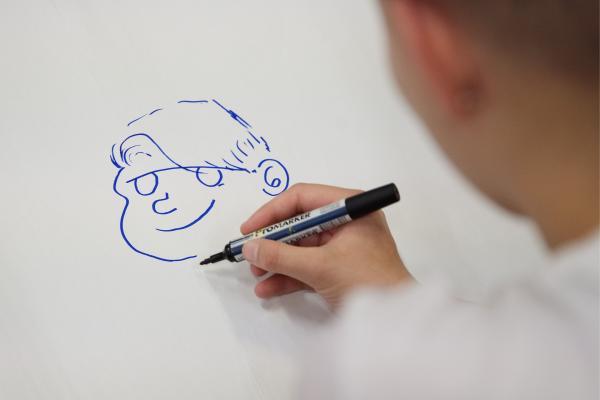 Kuvisuskuvassa käsi on piirtämässä kuvaa pojasta