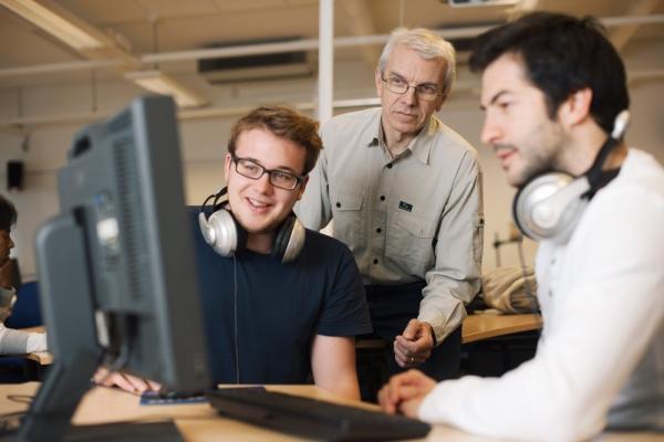 Kuvistuskuvassa kolme henkilöä katsoo tietokoneen näyttöä