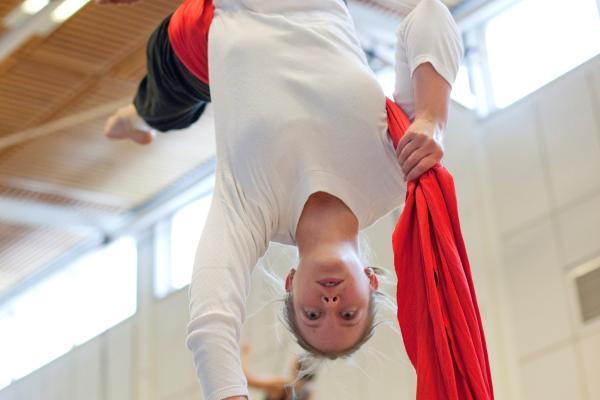 Kuvituskuvassa nuori nainen harjoittelee ilma-akrobatiaa