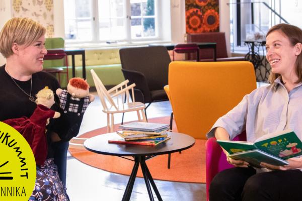 Lukukummit-logo, Annika Saarikko istuu käsinukkejen kanssa ja Li Andersson istuu vieressä kirjan kanssa