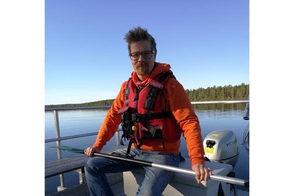 Mies järvellä veneessä pelastusliivit päällä ja mela kädessä.