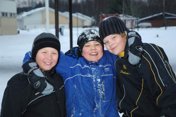 Kolme poikaa koulun talvisella pihalla.