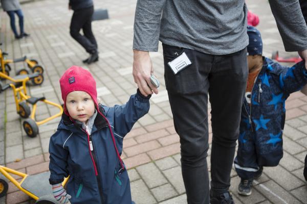 Lapsi pitää kiinni aikuisen kädestä päiväkodin pihalla.