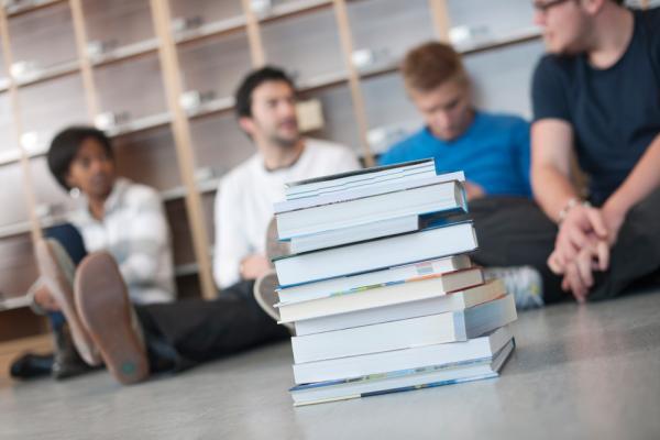 Kuvituskuvassa oppikirjapino ja opiskelijoita
