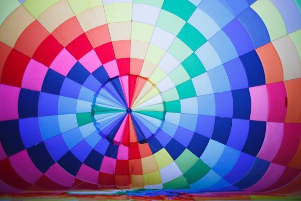 Värikäs kuumailmapallo, jossa sinisisä, vihreitä, punaisia, oransseja ja vaaleanpunaisia suorakulmioita.