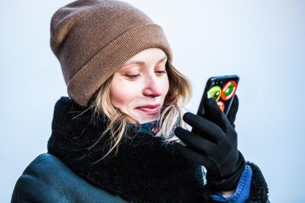 Kuvituskuvassa nainen katsoo puhelintaan