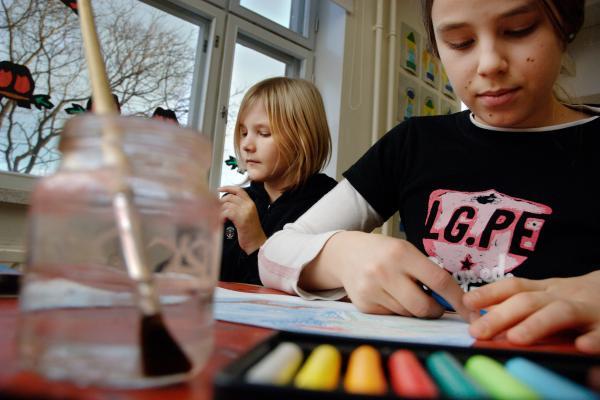 Lapset maalaamassa pöydän ääressä.