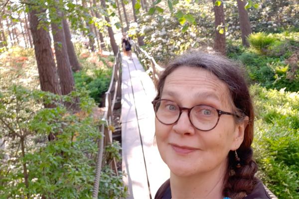 Tiina Hokkanen kesäisessä metsässä pitkospuilla