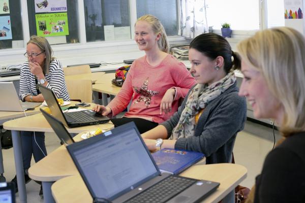 Neljä naisopettajaa pitää kokousta luokassa
