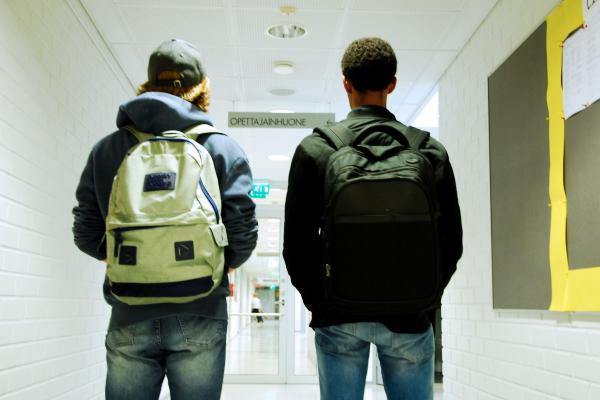 Kuvituskuvassa opiskelijanuorukaiset seisovat koulun käytävällä