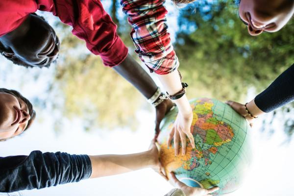 Nuoret pitävät käsissään puhallettavaa maapalloa
