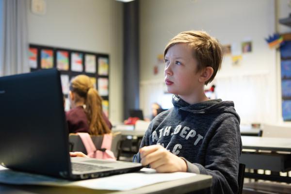 Poika miettii tietokoneen ääressä
