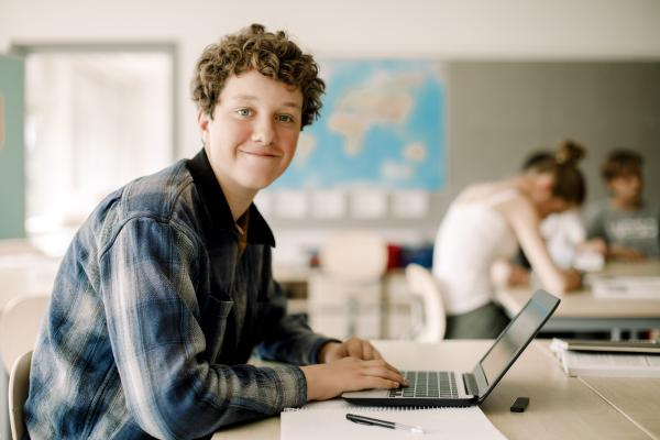 Opiskelija työskentelee kannettavalla tietokoneella