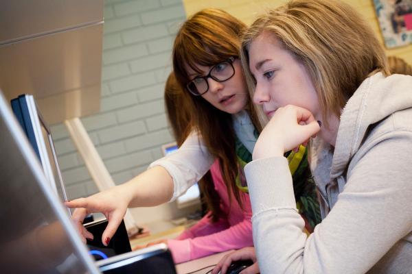Opettaja ja oppilaita tietokoneen ääressä.