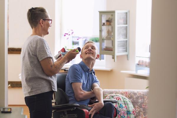 Kuvituskuvassa henkilökohtainen avustaja auttaa nuorta pyörätuolissa