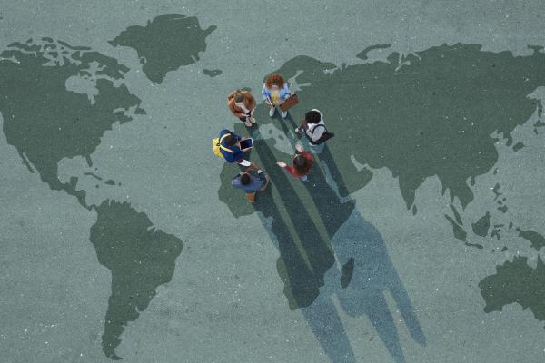 Opiskelijat seisovat maailman kartan päällä