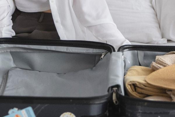 Henkilö istuu puoliksi pakatun matkalaukun äärellä.