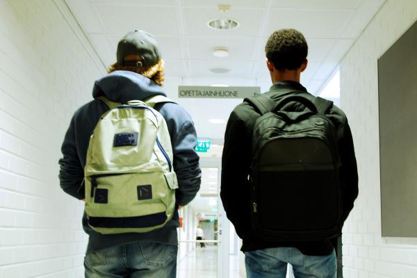 Två pojkar med ryggsäckar på ryggen (bakifrån)