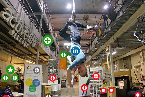 Kuvassa ilma-akrobaatti roikuu köydessä pää alaspäin messuhallissa.