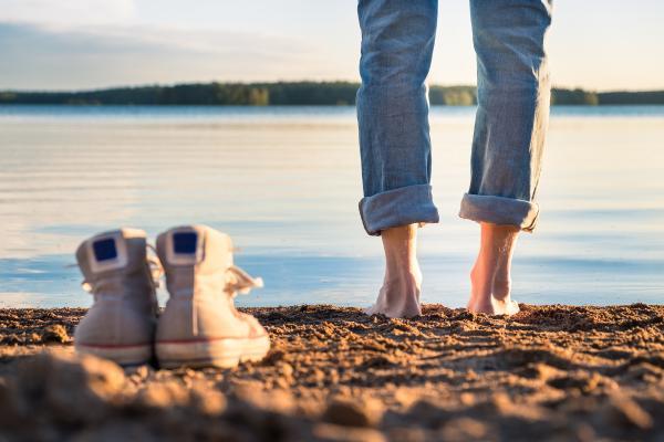 Tennarit ja jalat rannalla