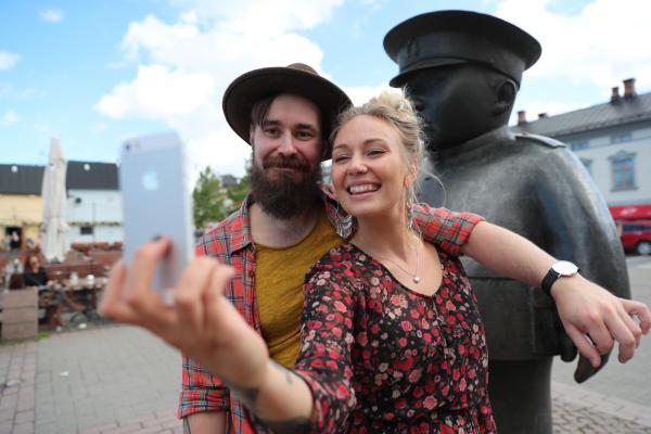 Hymyilevä pariskunta ottaa kaulakkain selfietä puhelimella Oulun keskustassa Toripolliisi-patsaan edessä.