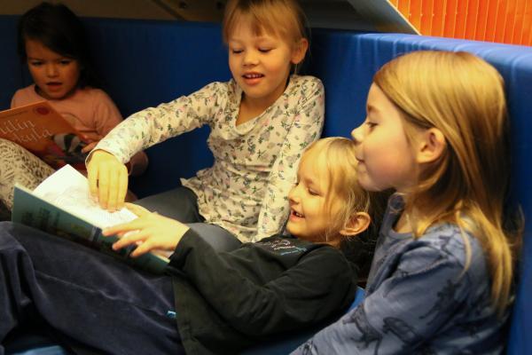 Lapsia lukemassa kirjaa yhdessä.