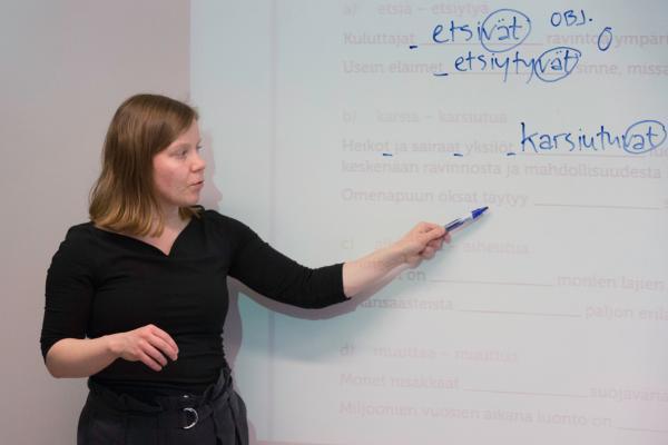 Opettaja näyttää taululta suomen kielen tehtävää
