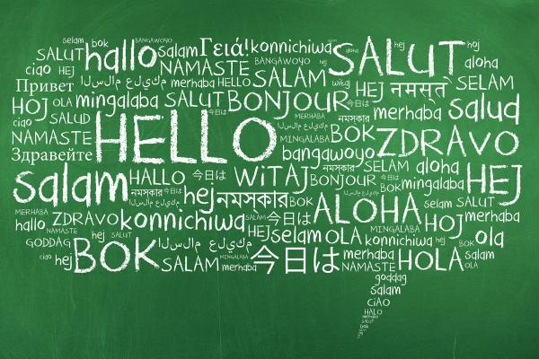 Hälsningar på olika språk i en pratbubbla på en svart tavla