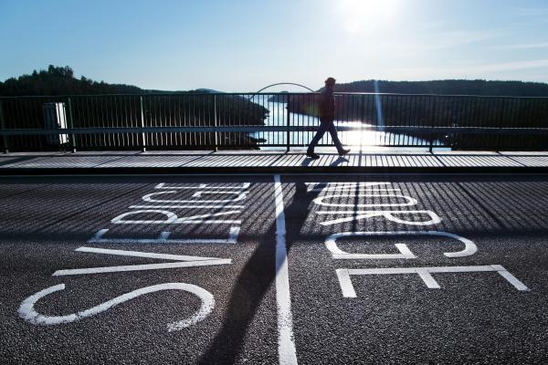 Ihminen kävelee jalkakäytävällä auringon paisteessa, Ruotsin ja Norjan rajan yli.