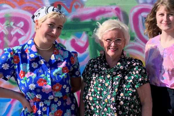 Merja Tervo seisoo graffitiseinän edessä kahden nuoren vapaaehtoisen kanssa.