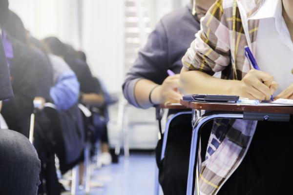 Oppilaita kirjoittamassa pöytien ääressä