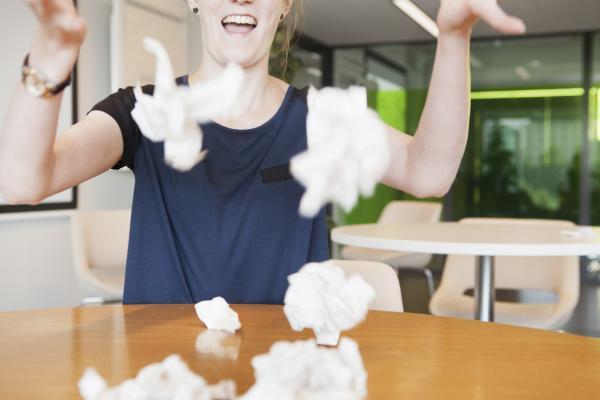 Nainen heittelee iloisesti paperia.