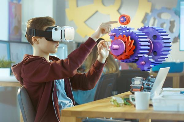 Kuvituskuva. Poika mallintaa virtuaalilaseilla vaihdejärjestelmää.
