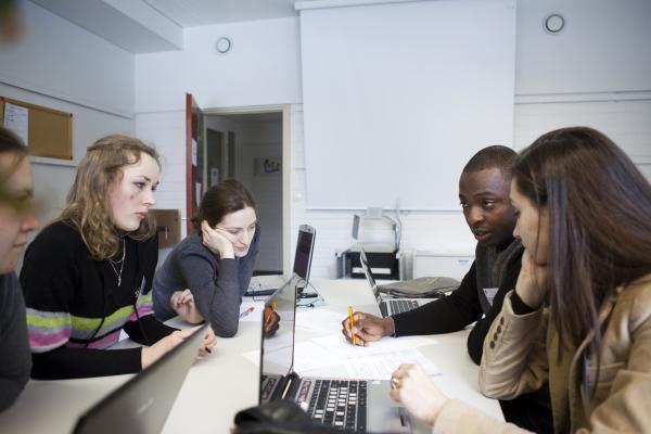 Korkeakouluopiskelijoita keskustelee pöydän ääressä