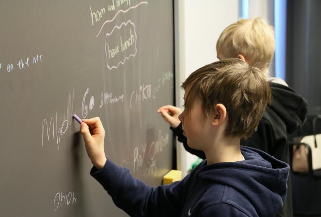 Kuvituskuva, poika kirjoittaa liitutaululle