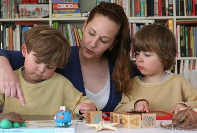 Kuvituskuva, lapset lukevat aikuisen kanssa