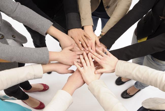 Kuvituskuvassa kehässä seisovat ojentavat kätensä kohti ypmyrän keskipistettä
