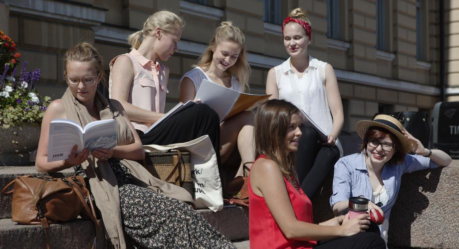 Students sitting on the stairs of the University of Helsinki main building