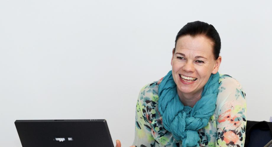 A teacher at a computer smiling