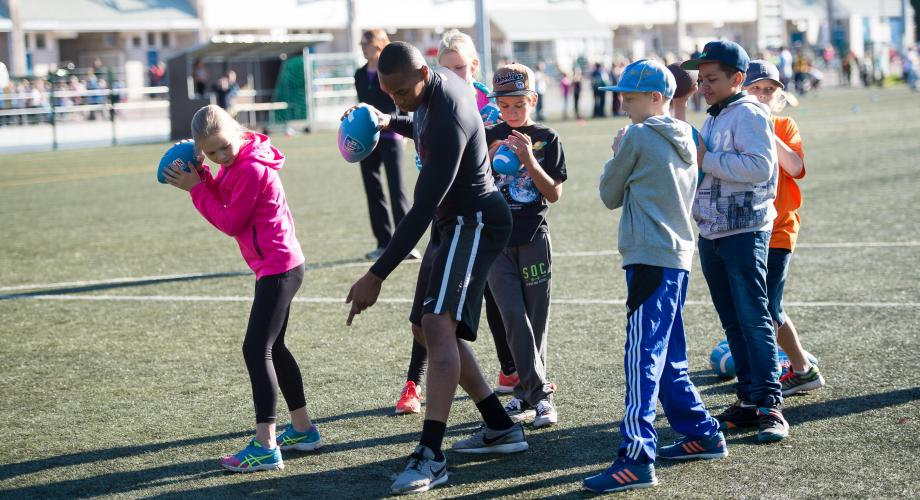 Children learning to throw an American football