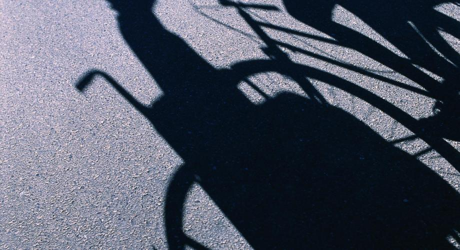 The shadows of a person in a wheelchair and a bicyclist