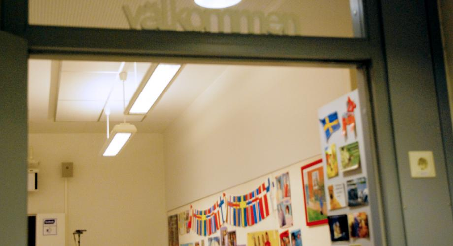 "Picture of an open classroom door with the text ""welcome"""
