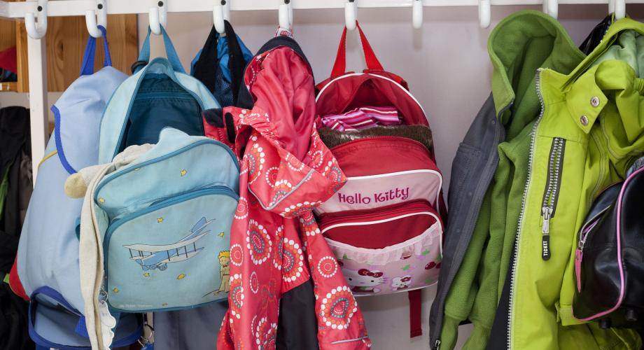 Colourful school bags hanging in a clothes rack in the school corridor
